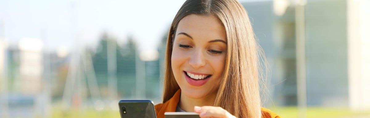 Mujer con tarjeta de Membresía de SABEResPODER y su telefono movil