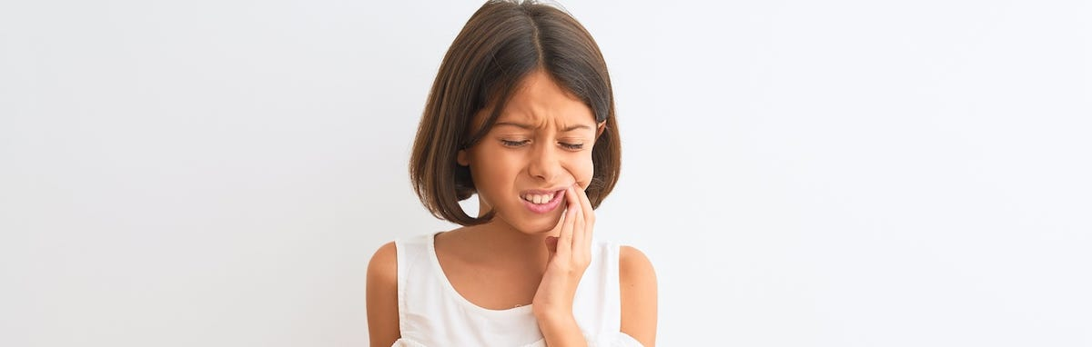 Una niña con dolor de dientes quien necesita tratamiento de salud bucal