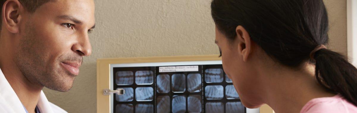 Dentista con un paciente en una consulta, explicando los beneficios de la prevención