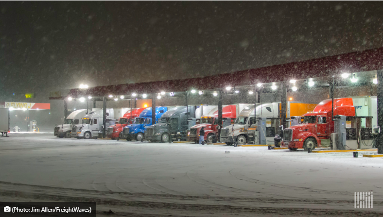 photo of trucks lined up at truck stop at night during snow storm