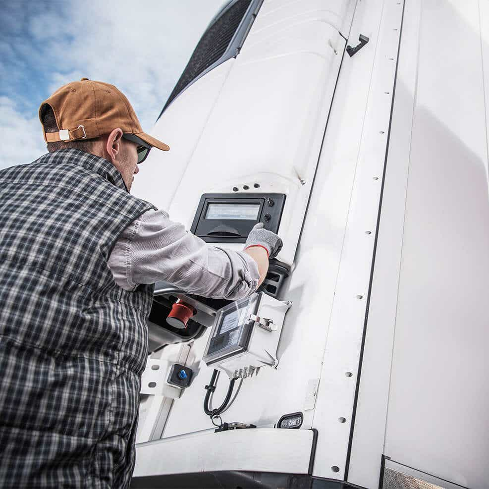 driver setting the temperature on a reefer truck for delivery