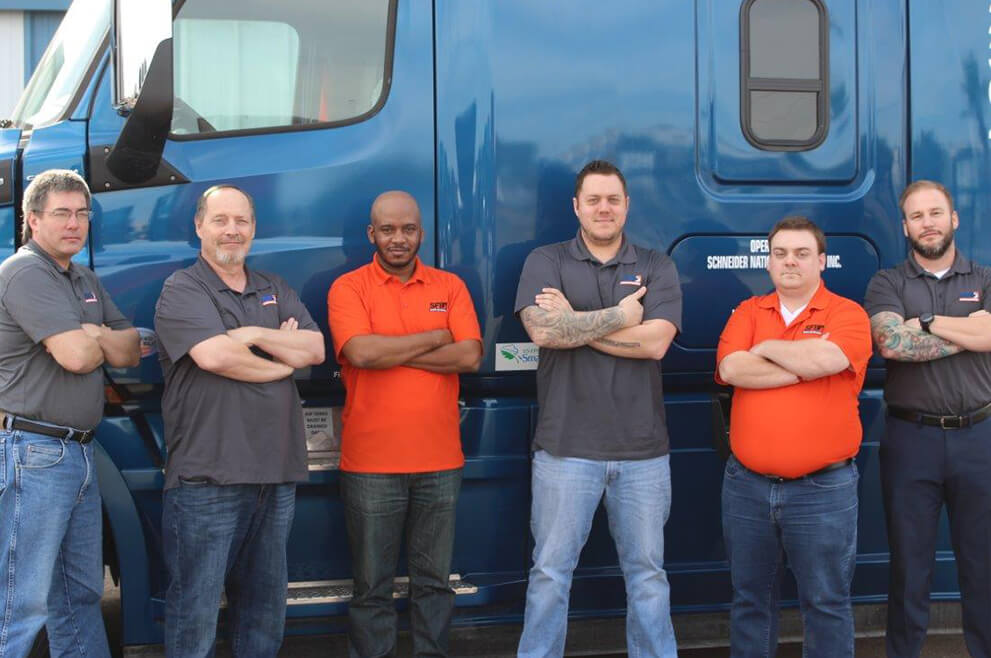 SFI employees and truck drivers stand in front of a semi-truck