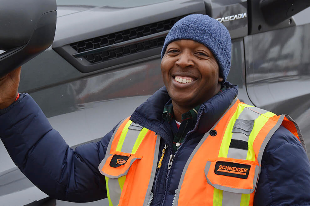 Truck driver standing in front of his semi-truck