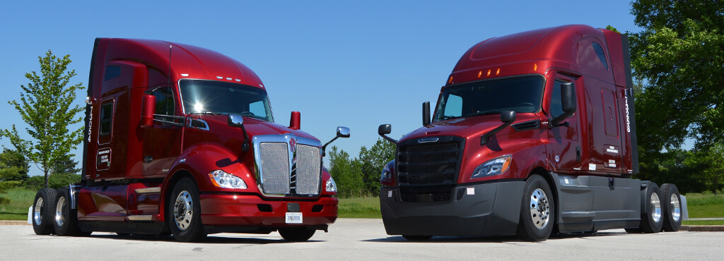 two red semi trucks parked next to each other ready to be leased.