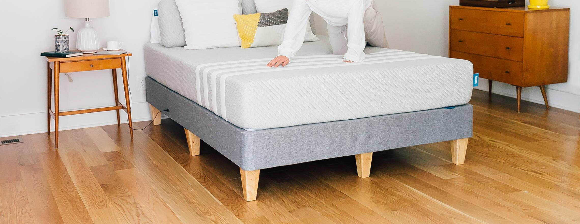 lady_climbing_onto_a_leesa_mattress_in_a_decorated_room