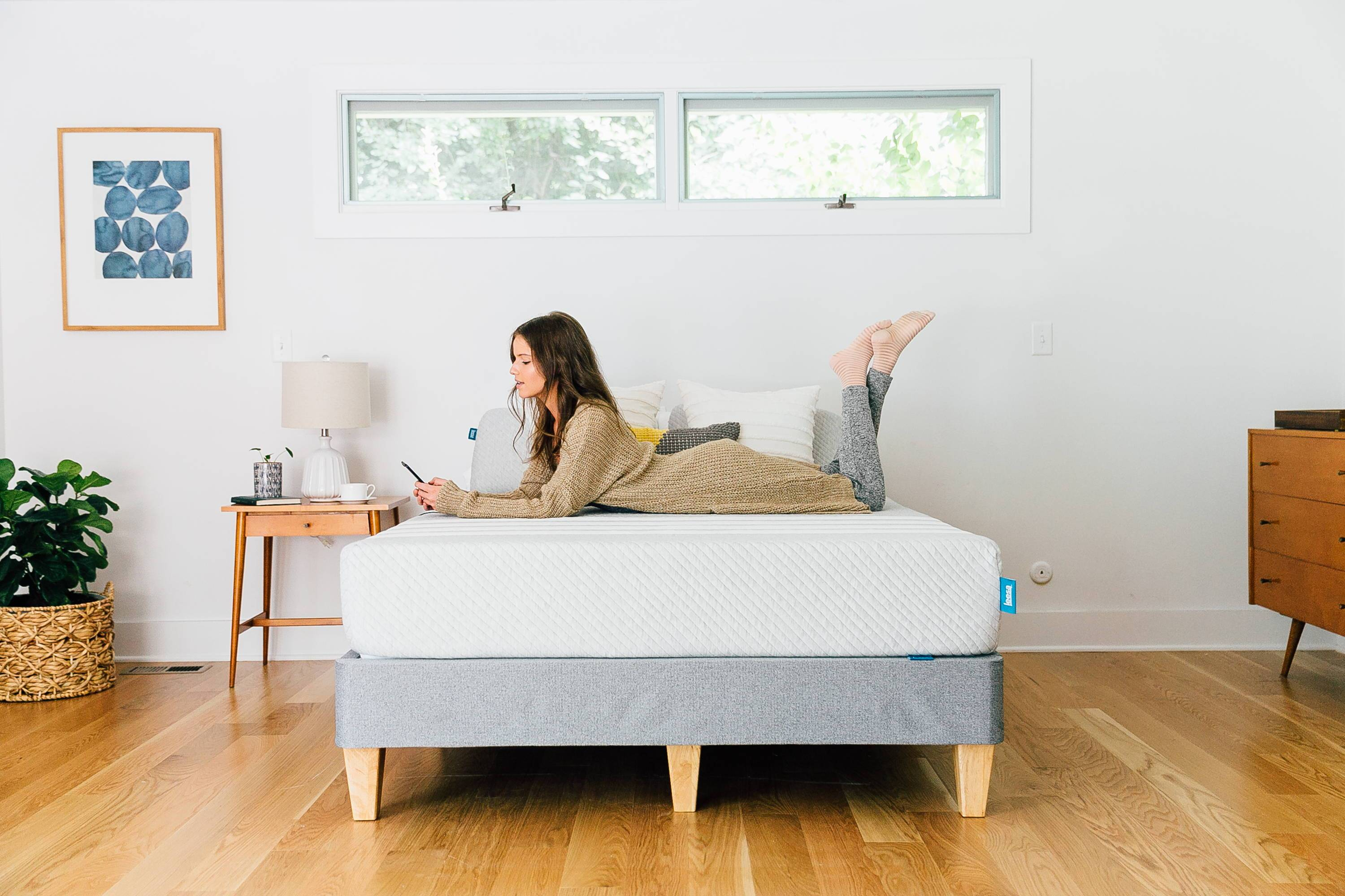 a_lady_laying_on_a_leesa_mattress_in_a_decorated_room