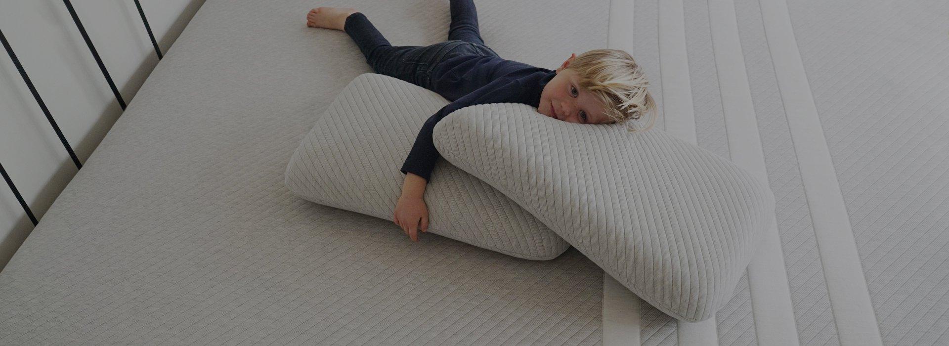 Leesa vs. Casper.  Boy on a Leesa mattress and pillows.