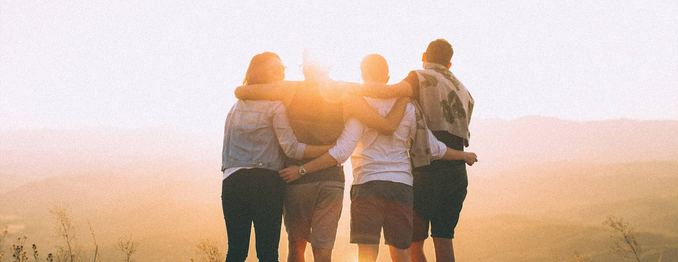 group_of_people_standing_arm_in_arm_looking_into_the_sunset