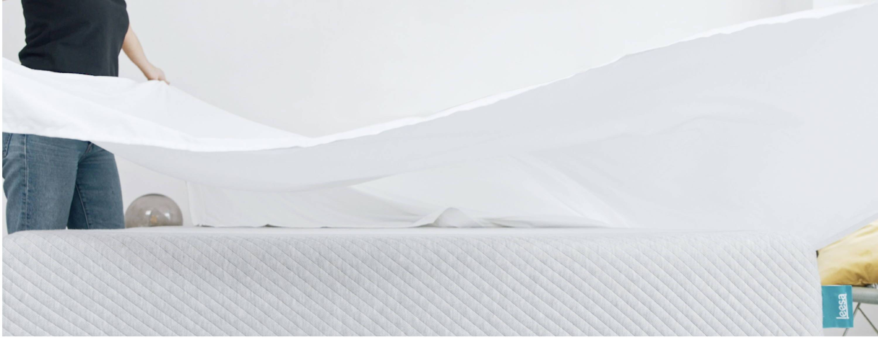 lady_fluffing_white_sheets_on_a_leesa_mattress_close_up_view