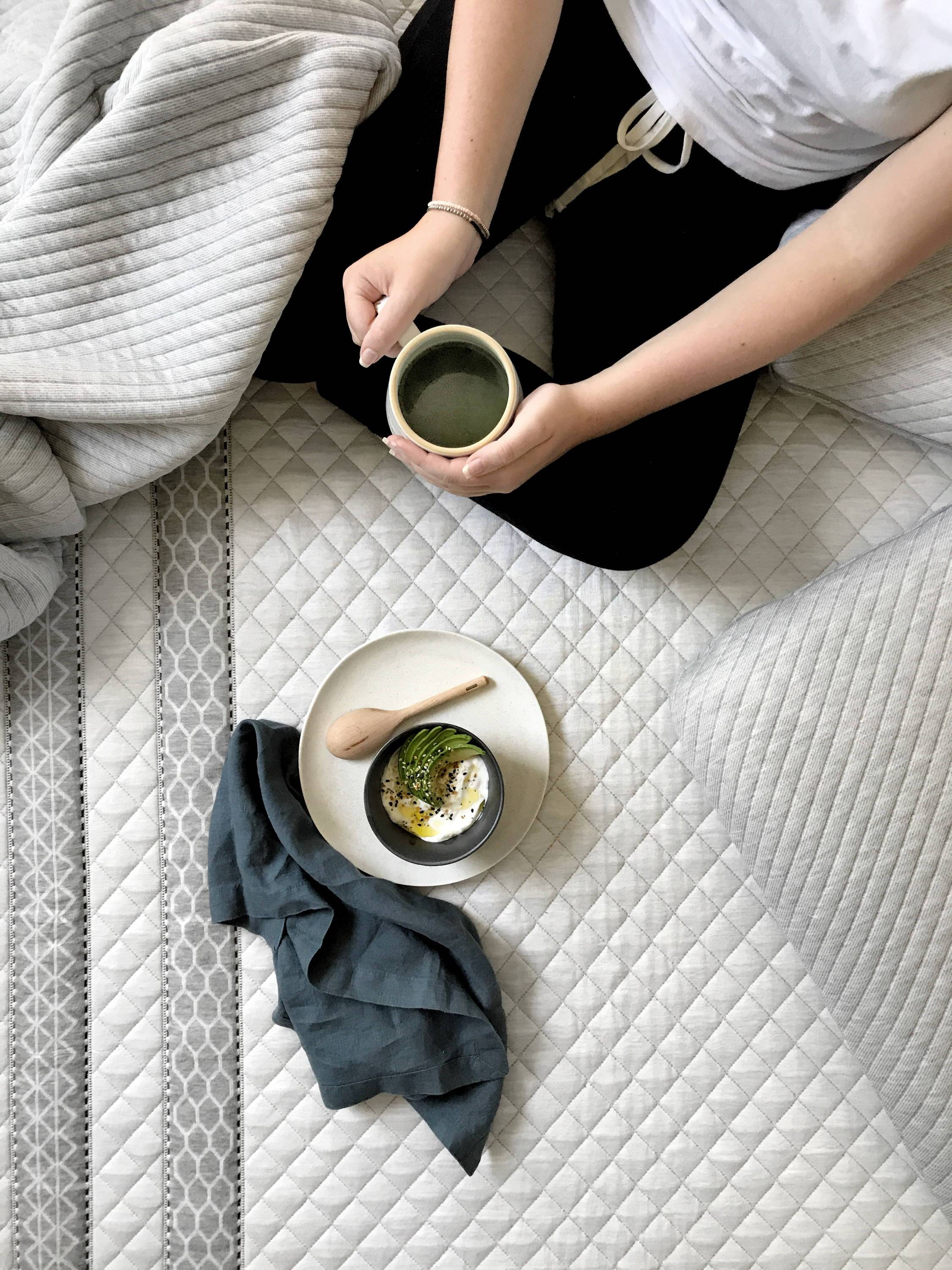 lady_sitting_on_bed_with_coffee_and_a_plate_of_sliced_avocado_and_eggs