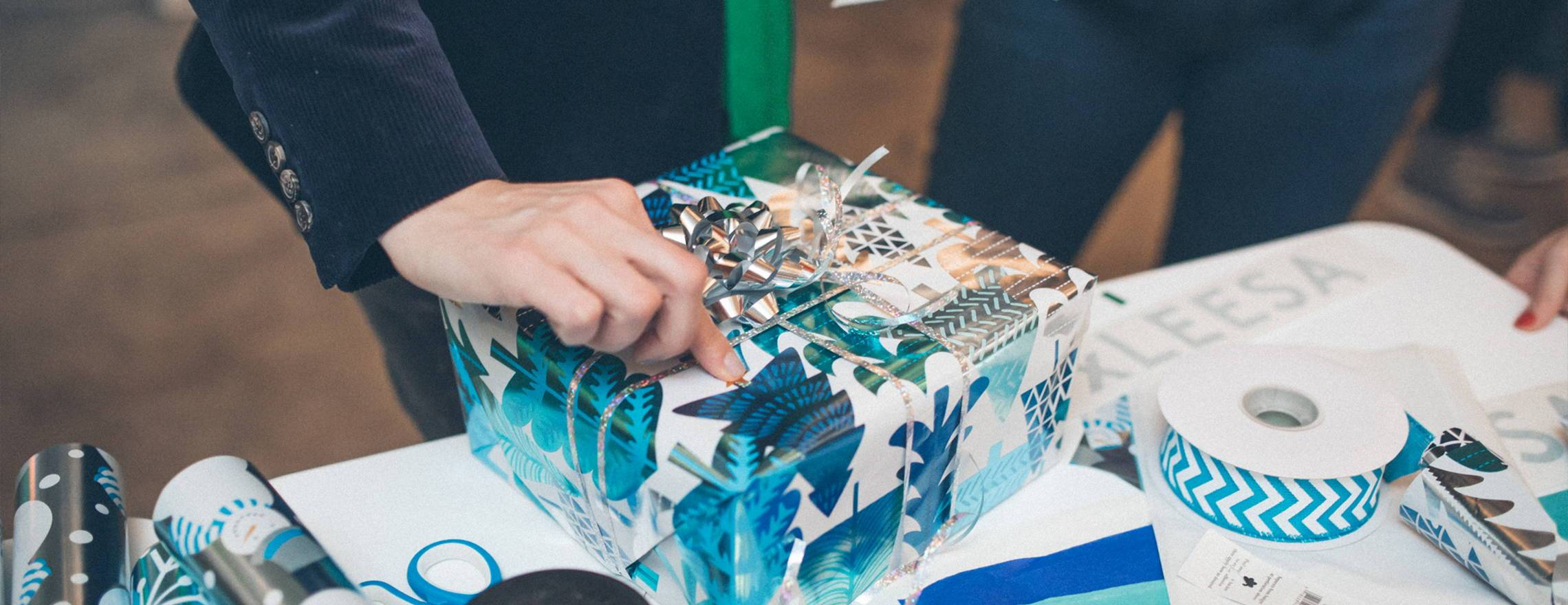 a_hand_on_a_blue_and_white_christmas_present
