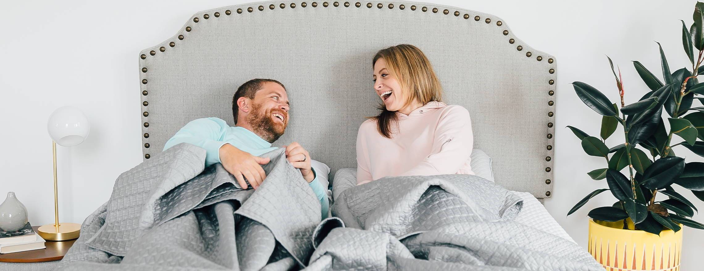 couple_laughing_in_gray_bedding_and_headboard_on_a_leesa_mattress_1