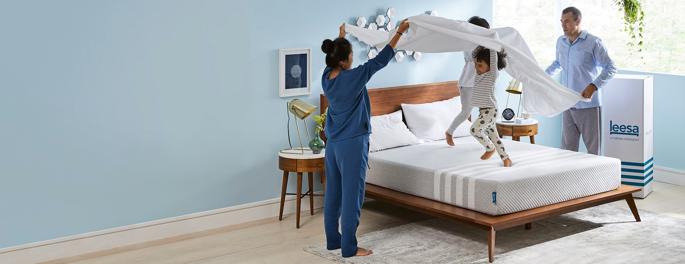 family_playing_on_a_leesa_mattress_in_a_blue_bedroom_1