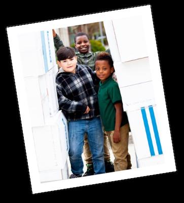 Polaroid of kids standing next to Leesa mattress boxes