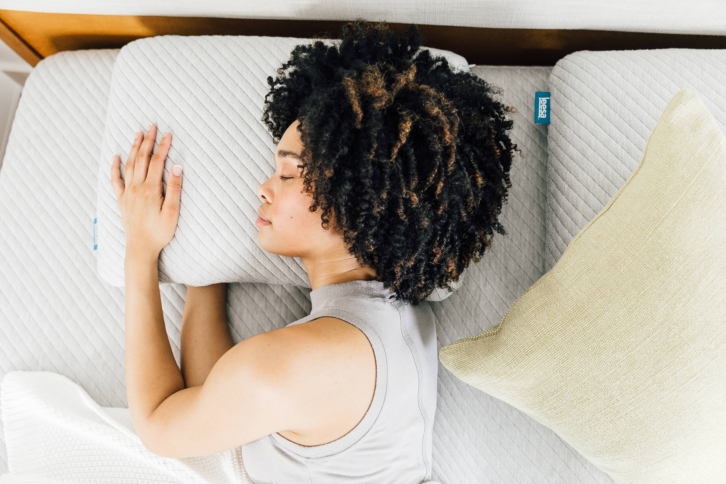 a_lady_sleeping_on_her_side_on_a_leesa_gray_mattress_and_pillow_2