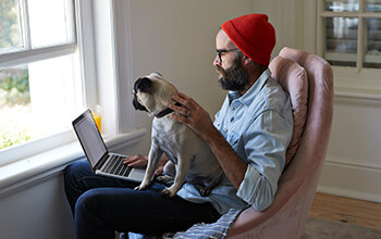 A man with a red beanie on his head sits on a chair with a laptop and pug on his lap.