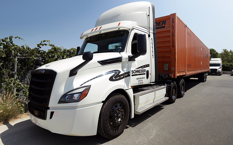 A white eCascadia semi-truck hauling an orange Intermodal container is parked at a California facility.