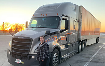 Tanaya Everbe wears a plaid shirt and stands in front of her grey Freightliner Cascadia truck hauling an orange Schneider trailer. There is an orange sunset in the background.