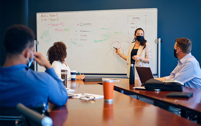A women stands at a white board while wearing a face mask and presents to a group of men and women who are also wearing face masks.