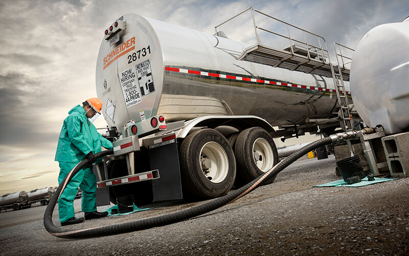 A Schneider Tanker truck driver in a blue HazMat suit unloads liquid bulk freight from a tanker truck using a large hose.
