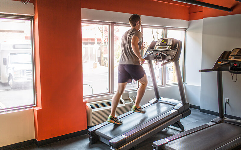A man wearing workout attire runs on an inclined treadmill at a gym.