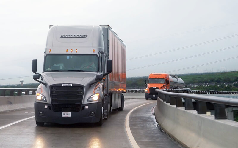 A grey Schneider Freightliner semi-truck hauling a dry van trailerdrives on an elevated highway overpass. An orange Schneider semi-truck hauling a tanker truck follows behind the first truck.