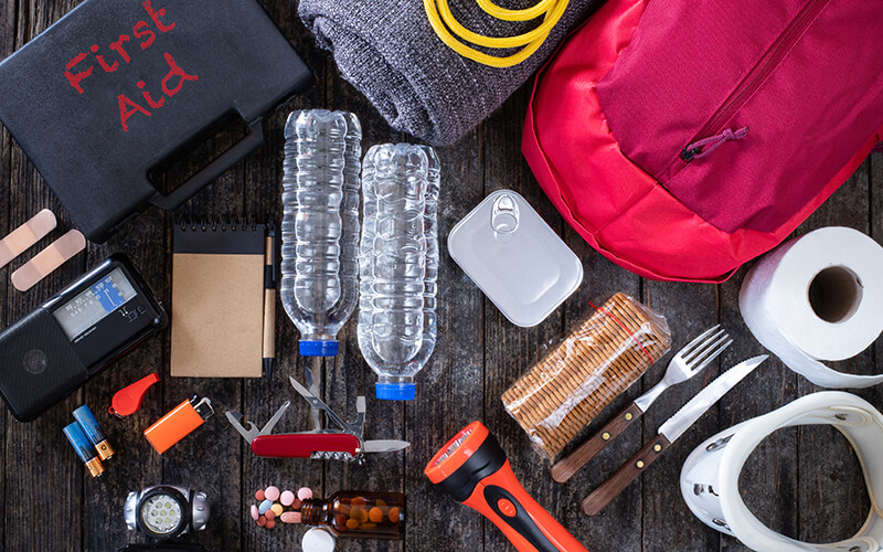 An abundance of survival items are laid out on a table, including a back pack, roll of toilet paper, utensils, snacks, water bottles, utility knife, lighter, batteries, headlight, flash light, bottle of pills, whistle, AM/FM radio, notebook and more.