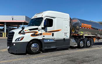 A white Schneider semi-truck hauling a chrome Schneider tanker trailer is parked at a fuel station.