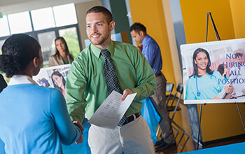 A man shakes hands with a woman and hands her his resume while attending a career fair.