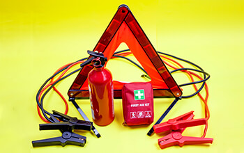 A grouping of must-have survival items are laid out on a table, including emergency triangles, fire extinguisher, jumper cables and a first aid kit.