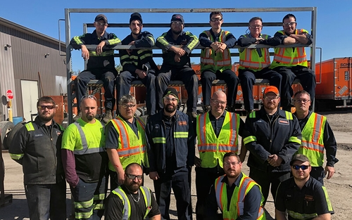 15 Schneider diesel technicians pose for a picture outside of a Schneider shop.