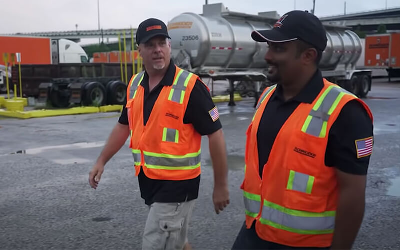 A Driver Mentor and his mentee wearing black shirts, orange safety vests and black baseball hats, walk in a truck yard.