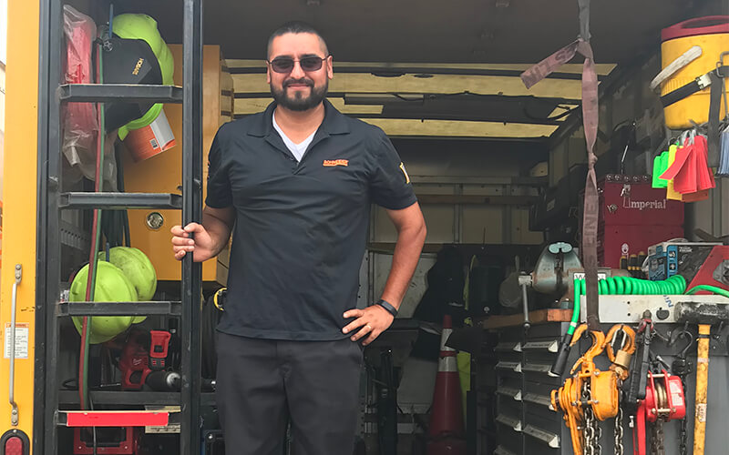 A Schneider service truck technician stands in the trailer of a Schneider service truck that is filled with various tools and equipment.