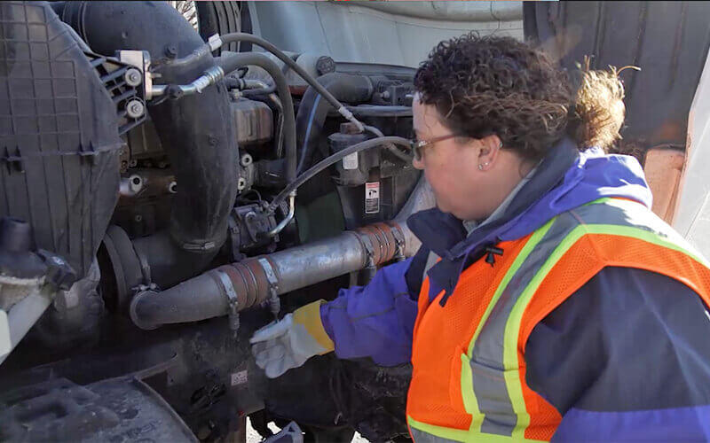 Schneider Driver Instructor Dana performs a CDL pre-trip inspection.