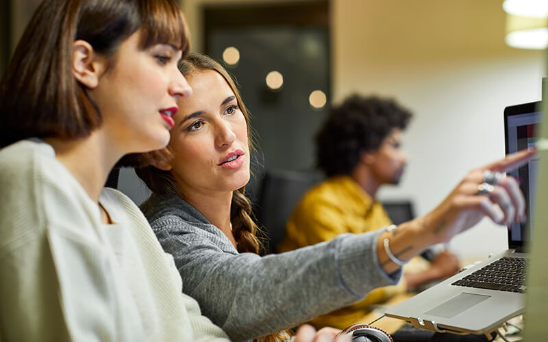 Two women sit near one another at a desk and converse about something that is on one of their computer screens. One of the women is pointing at the screen, and a man sits in the background working at his computer.