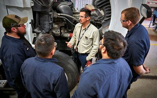 A group of four Schneider diesel technicians stand in a semi-circle around their training leader, who is talking, near a Schneider tractor.