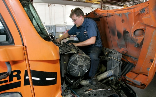A Schneider Diesel Technician works on an engine of a Schneider truck.