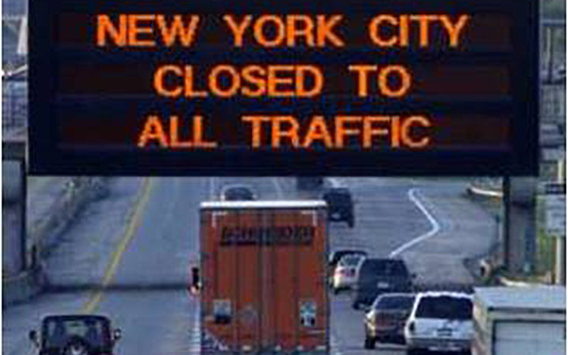 """Schneider truck on highway driving under a sign that says """"New York city closed to all traffic"""""""