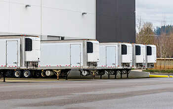 Five white drop-and-hook reefer trailers sit at the loading dock of a business, waiting to be unloaded.