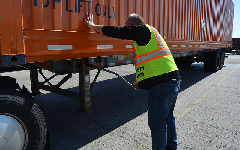 A driver wearing a black long sleeved shirt, safety vest and jeans cranks the landing gear of an Intermodal trailer.