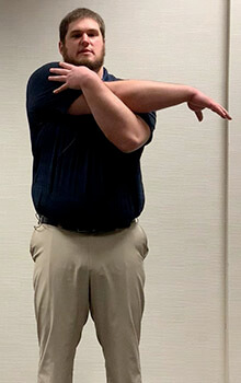 A physical therapist demonstrates stretching his shoulder by reaching is right arm across his body and grabbing his right shoulder with his left hand.