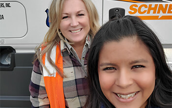 Two women take a selfie in front of a white Freightliner Cascadia that has the Schneider logo on the side of it.