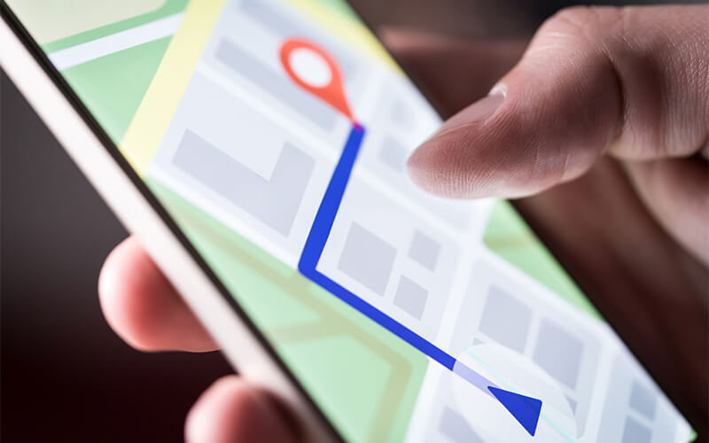 A person holds a phone displaying a visual of a GPS route.