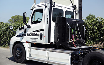 A white eCascadia truck is parked at an angle at a California facility. The tractor is not hooked up to a trailer, so the side batteries and plugs on the back of the truck are visible.