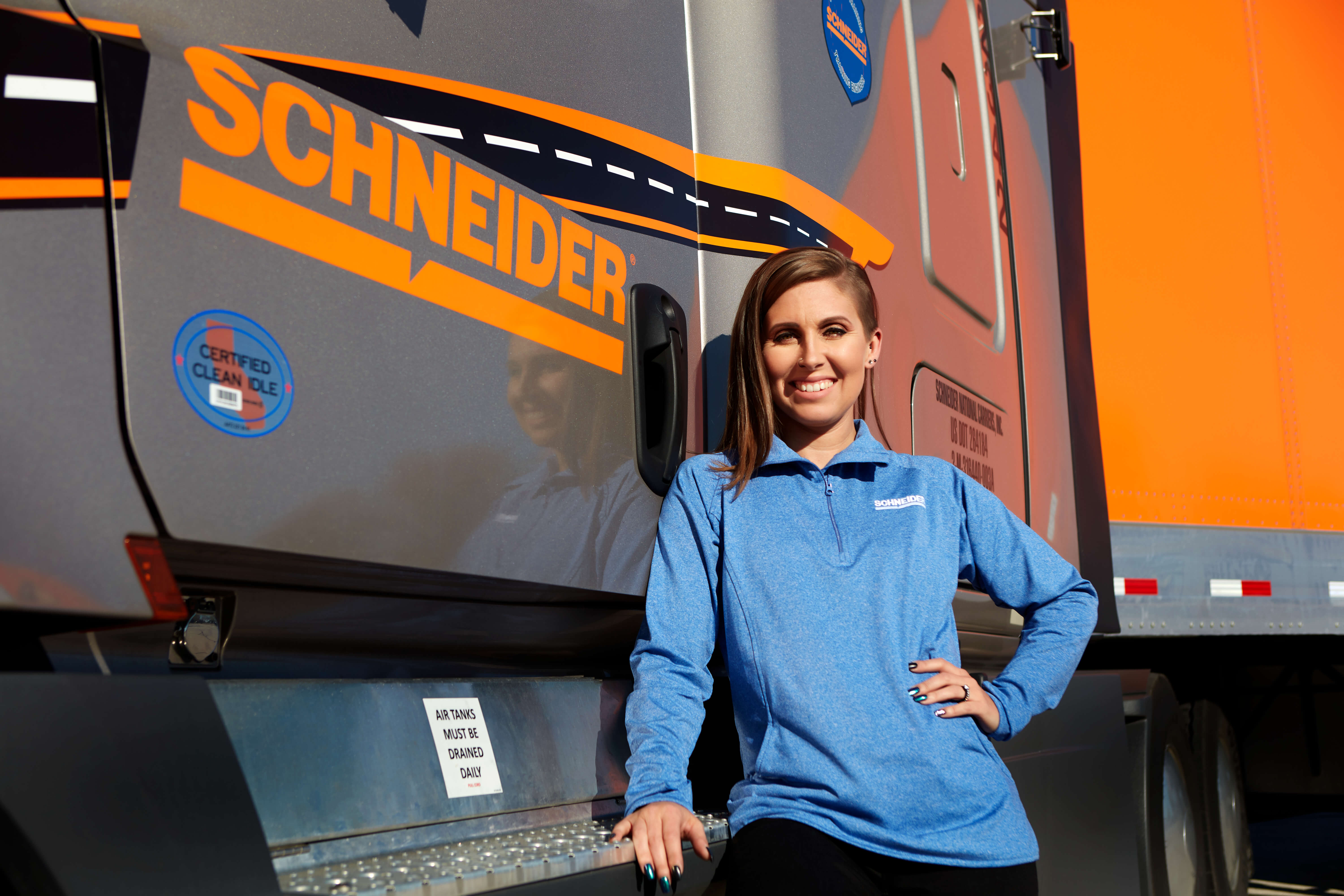 KayLeigh McCall poses in front of a champagne-colored Schneider tractor and an orange Schneider trailer.