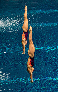 Krysta Palmer and Alison Gibson, dive head first-into a pool.