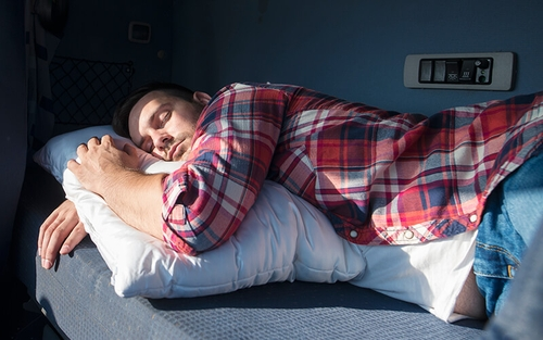 A young man wearing a plaid button-up shirt and jeans takes a mid-day nap in the sleeper of a semi-truck.