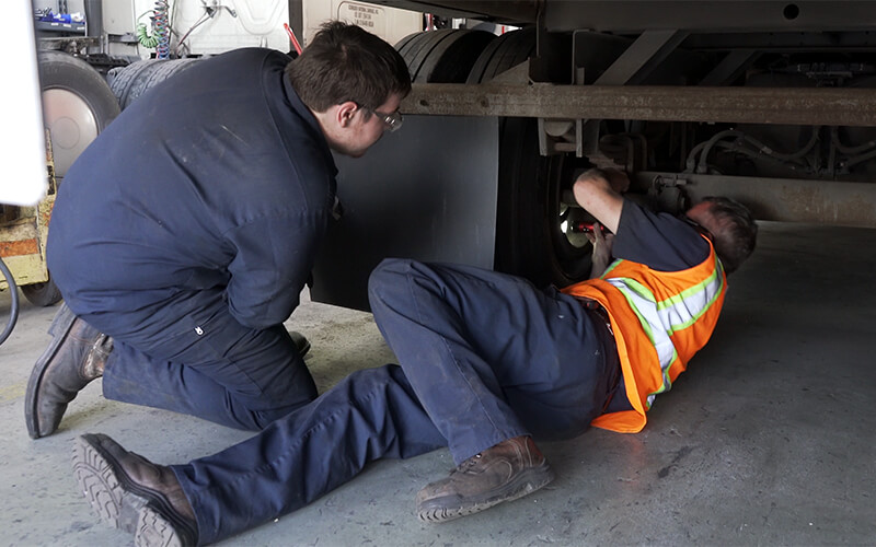 A Schneider diesel technician works on repairing the underside of a semi-trailer while his leader supervises.