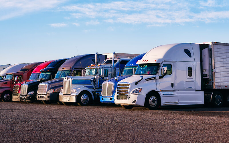 A variety of semi-trucks are parked side-by-side in a gravel parking lot.