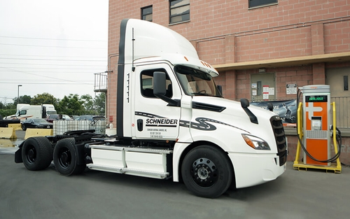 A white electric semi-tractor trailer is parked next to its charging station outside of one of Schneider's California operating centers.